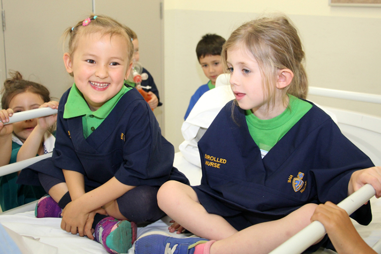 Two pre-primary school girls sitting on a hospital bed