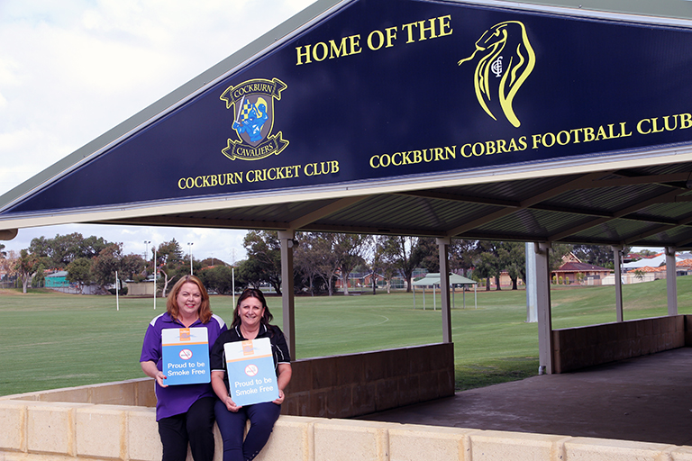 Two women holding signs that read 'Proud to be Smoke Free'. The women are seated underneath a sign that reads 'Home of the Cockburn Cricket Club and Cockburn Cobras Football Club'
