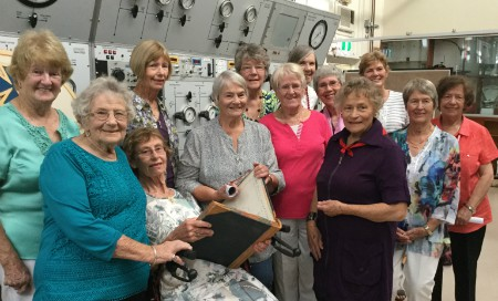 A group of older women looking at old nursing records