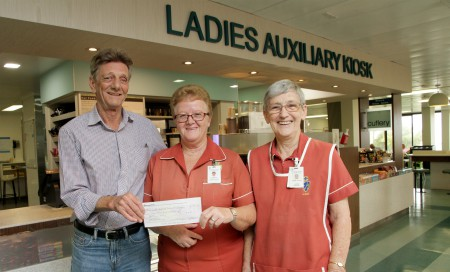 A man presenting a cheque to two women under a sign for the Ladies Auxiliary Kiosk