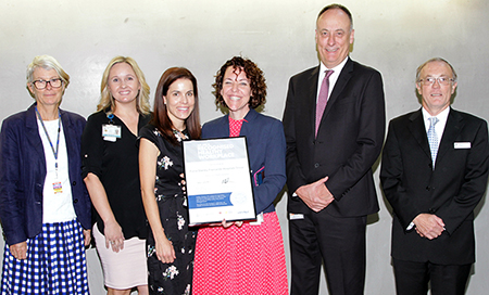 Six people standing side by side. One woman is holding a framed certifiicate