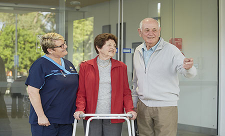 Nurse standing with elderly couple outside hospital entrance