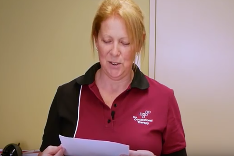 Occupational therapist reading from piece of paper