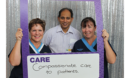 Two female and one male health professional holds a sign that reads 'Compassionate care to patients'.