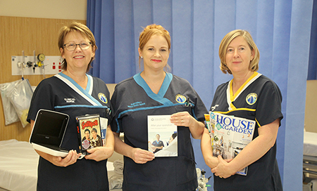 Three female nurses in Rockingham General Hospital uniforms standing in a treatment area