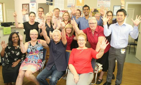 Members of the Rockingham Endocrinology and Diabetes Service team raise their hands in celebration