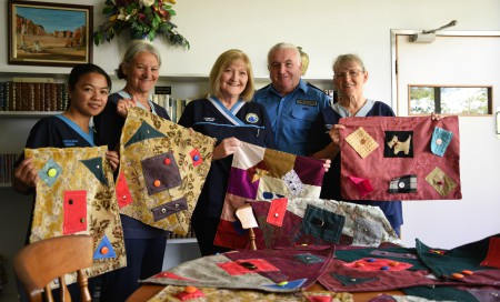 Four medical staff and one prison officer holding hand quilted fiddle mats