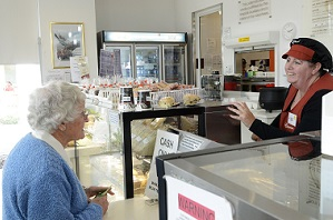 An older woman ordering food at the counter of a food outlet